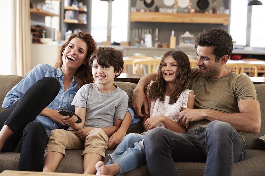 film per ridere con famiglia, famiglia sorridere sul divano